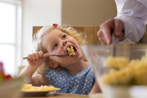 A little girl can be seen sat at the dinner table at home eating pasta for her dinner, she looks very happy and content as she look up at her dad dishing out the food.