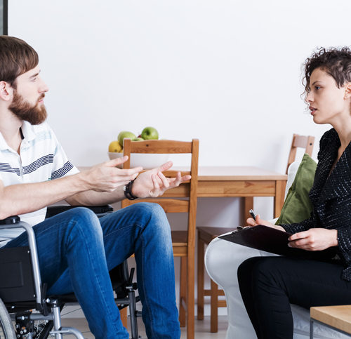 Young bearded man in wheelchair talking with psychotherapist at home